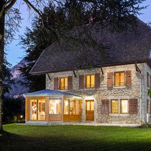 Cette photo montre une grand façade en pierre beige nature à deux étages et plus avec un toit à croupette.