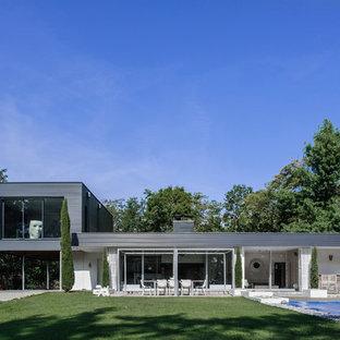 Idée de décoration pour une façade de maison blanche minimaliste à niveaux décalés avec un revêtement mixte et un toit plat.