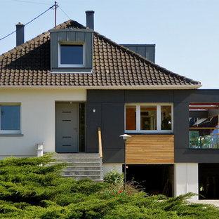 Exemple d'une façade de maison multicolore tendance à un étage avec un revêtement mixte, un toit à quatre pans et un toit en tuile.