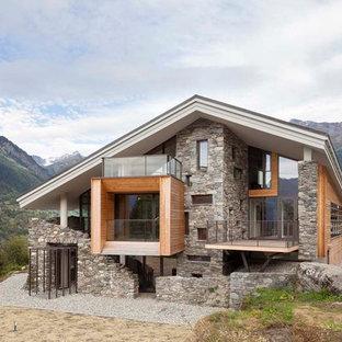 Cette image montre une grande façade de maison design à deux étages et plus avec un toit à deux pans et un revêtement mixte.