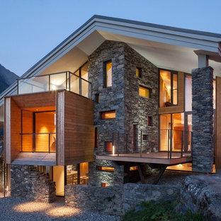 Cette image montre une grand façade de maison chalet à deux étages et plus avec un toit à deux pans et un revêtement mixte.