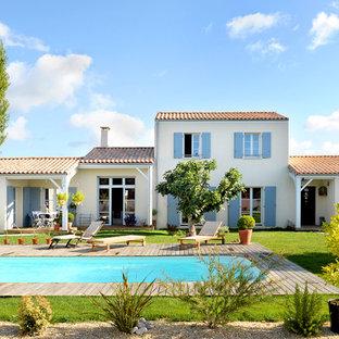 Cette photo montre une grande façade de maison beige méditerranéenne à un étage avec un toit à deux pans.