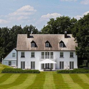 Cette image montre une très grande façade de maison blanche traditionnelle à deux étages et plus avec un toit à deux pans.