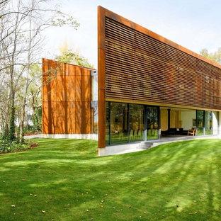 Cette image montre une grande façade en bois design à un étage avec un toit plat.