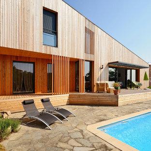Imagen de fachada marrón, contemporánea, de tamaño medio, de dos plantas, con revestimiento de madera y tejado de un solo tendido