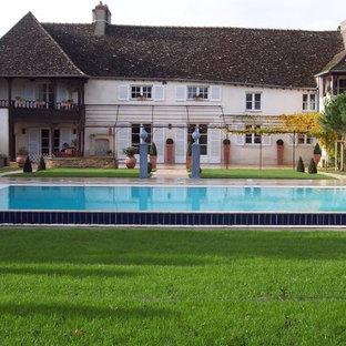 Aménagement d'une grand façade de maison beige campagne à un étage avec un toit à deux pans.