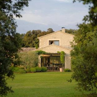 Aménagement d'une façade de maison beige méditerranéenne à un étage avec un toit à deux pans et un toit en tuile.
