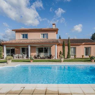 Cette image montre une façade de maison beige traditionnelle de taille moyenne et à un étage avec un toit à deux pans.