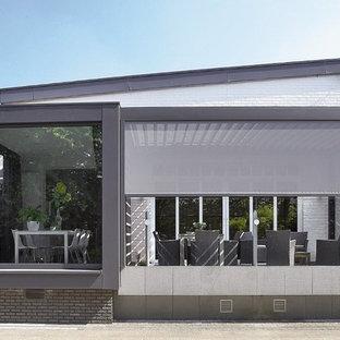 Idée de décoration pour une façade de maison grise minimaliste de taille moyenne et à un étage avec un toit en appentis.