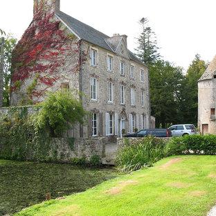 Réalisation d'une grande façade en pierre beige tradition à deux étages et plus avec un toit à deux pans.