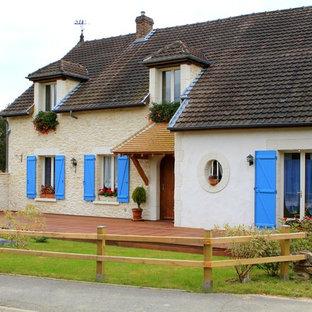 Idée de décoration pour une façade en pierre beige champêtre à un étage et de taille moyenne avec un toit à deux pans.