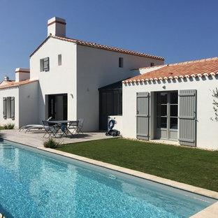 Cette image montre une façade de maison blanche méditerranéenne de taille moyenne et à un étage avec un toit à deux pans.