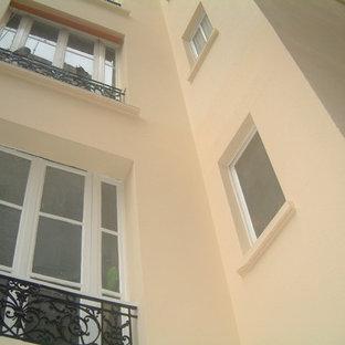 Ejemplo de fachada de casa pareada beige, tradicional, de tamaño medio, de tres plantas, con revestimiento de hormigón, tejado a doble faldón y tejado de teja de barro