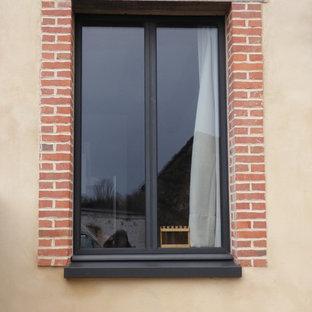 レンヌのカントリー風おしゃれな家の外観 (レンガサイディング、ベージュの外壁、寄棟屋根、デュープレックス、混合材屋根) の写真