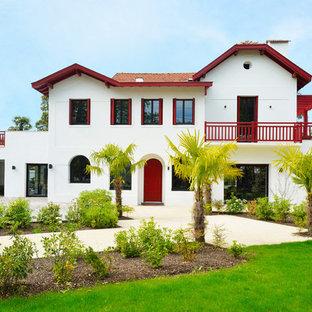 Exemple d'une grande façade de maison blanche exotique à un étage.
