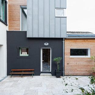 Exemple d'une façade de maison noire tendance de taille moyenne et à un étage avec un revêtement mixte et un toit en appentis.