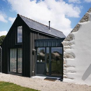 Cette photo montre une façade de maison noire tendance à un étage avec un revêtement mixte et un toit à deux pans.
