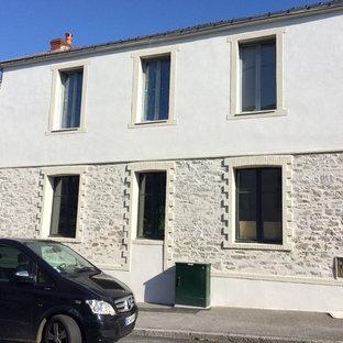 Modelo de fachada de casa pareada beige, bohemia, de tamaño medio, de dos plantas, con revestimiento de piedra, tejado a dos aguas y tejado de teja de barro