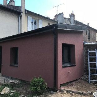 Modelo de fachada de casa pareada roja, ecléctica, pequeña, de dos plantas, con revestimientos combinados, tejado de un solo tendido y tejado de metal