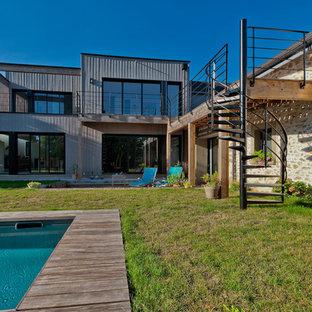Réalisation d'une grand façade de maison grise design à un étage avec un toit plat et un toit mixte.