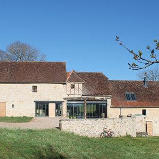 Réalisation d'une grande façade en pierre beige champêtre à deux étages et plus avec un toit à deux pans.