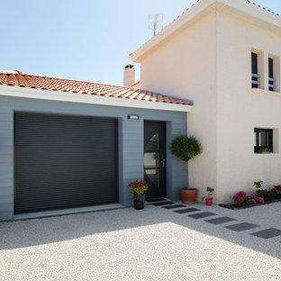 Cette image montre une grand façade de maison multicolore méditerranéenne à un étage avec un toit en tuile, un revêtement en stuc et un toit à quatre pans.