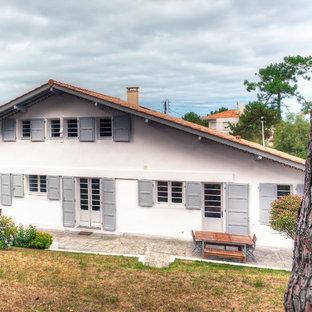 Cette photo montre une façade de maison blanche chic à un étage.