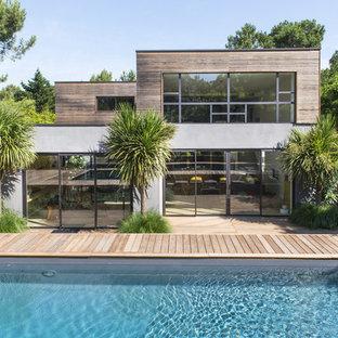 На фото: двухэтажный дом среднего размера в современном стиле с облицовкой из бетона и плоской крышей с