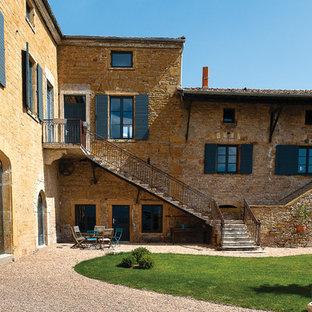 Cette photo montre une très grande façade en pierre jaune méditerranéenne à deux étages et plus avec un toit à deux pans.