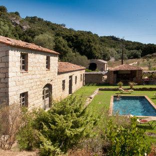 Réalisation d'une façade en pierre champêtre à niveaux décalés et de taille moyenne avec un toit à deux pans.