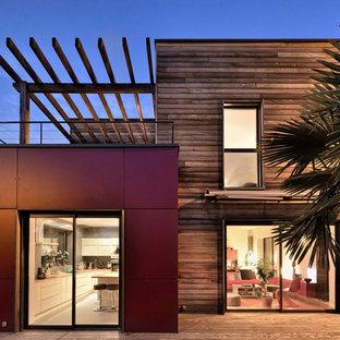 Cette photo montre une façade de maison rouge tendance à un étage avec un revêtement mixte et un toit plat.