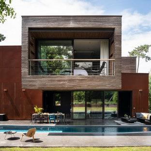 Immagine della facciata di una casa unifamiliare marrone moderna a due piani con rivestimenti misti e tetto piano
