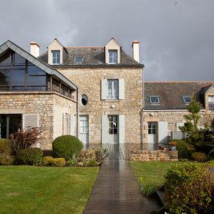 Cette photo montre une façade en pierre beige chic de taille moyenne et à deux étages et plus avec un toit à deux pans.