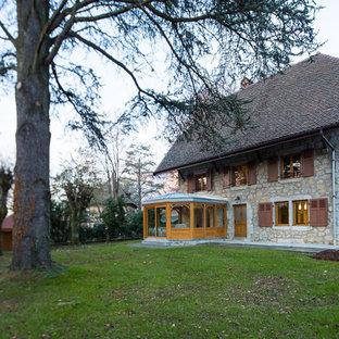 Inspiration pour une façade en pierre grise rustique de taille moyenne et à deux étages et plus avec un toit à croupette.