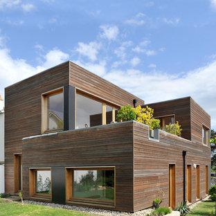 Idées déco pour une façade en bois marron contemporaine de taille moyenne et à un étage avec un toit plat.
