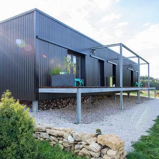 Idée de décoration pour une façade de maison grise urbaine de taille moyenne et de plain-pied avec un toit plat.