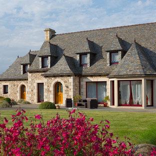 Cette photo montre une façade en pierre beige chic à un étage et de taille moyenne avec un toit à quatre pans.