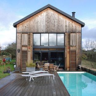 Cette photo montre une façade de maison marron nature à un étage et de taille moyenne avec un toit à deux pans.