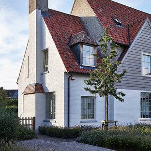 Idées déco pour une grand façade en brique blanche campagne à un étage avec un toit à deux pans.