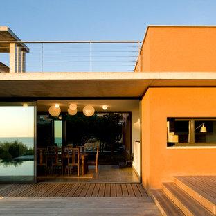 Inspiration pour une façade de maison orange méditerranéenne de taille moyenne et à un étage avec un toit plat.