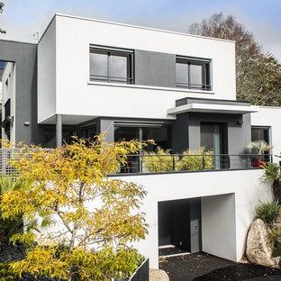 Aménagement d'une grand façade en béton blanche moderne à deux étages et plus avec un toit plat.