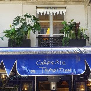 パリのトロピカルスタイルのおしゃれな家の外観 (石材サイディング、ベージュの外壁、腰折れ屋根、アパート・マンション) の写真