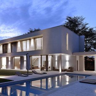 Inspiration pour une grande façade de maison grise minimaliste à un étage avec un toit plat.