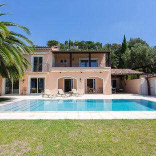 Idée de décoration pour une grande façade de maison beige méditerranéenne à un étage avec un toit à deux pans.