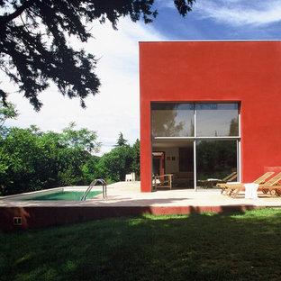 Réalisation d'une façade de maison rouge minimaliste de taille moyenne et à un étage avec un toit plat.