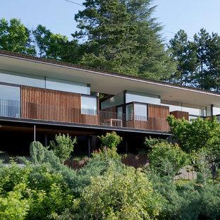 Inspiration pour une grand façade en bois marron design à un étage avec un toit plat.