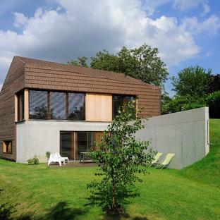 Inspiration pour une façade en bois marron design à un étage avec un toit à deux pans.