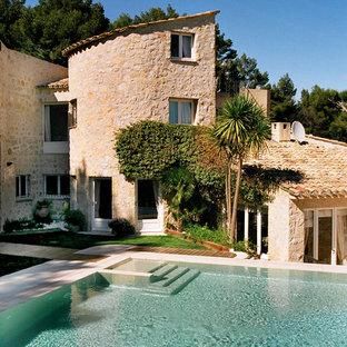 Exemple d'une façade en pierre beige méditerranéenne de taille moyenne et à deux étages et plus avec un toit en appentis.