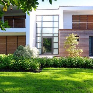 Aménagement d'une façade de maison blanche contemporaine à un étage avec un toit plat et un revêtement mixte.