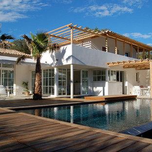 Réalisation d'une grand façade de maison blanche marine à un étage avec un toit à quatre pans.